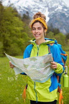 Smiling tourist enjoys travel in high mountains, holds paper map, searches way, wander across green meadow