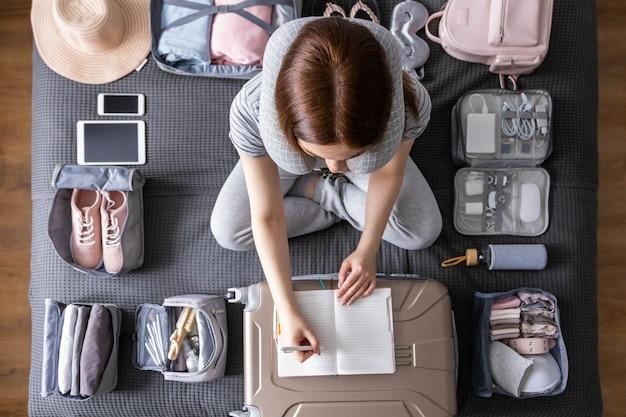Улыбающаяся туристка упаковывает чемодан в отпуск, пишет список бумаг, готовится к путешествию