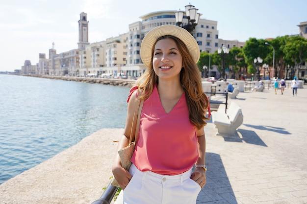 バーリ遊歩道、プーリア、イタリアを散歩する笑顔の観光客の女性