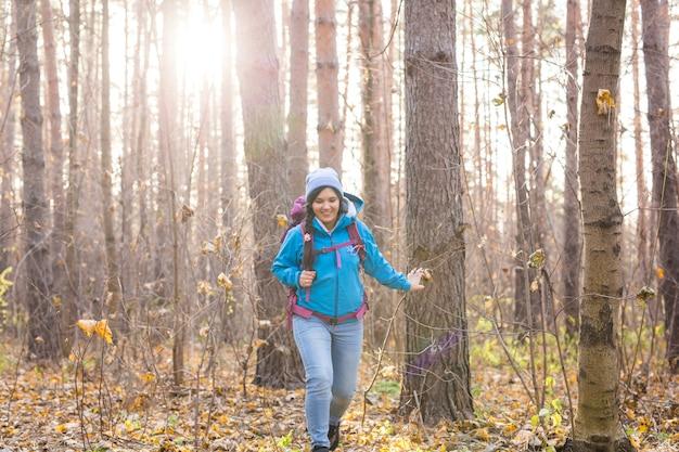 秋の自然な背景の上にバックパックを持って歩く観光客の女性の笑顔。