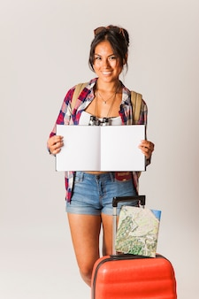 Smiling tourist woman with suitcase and open book
