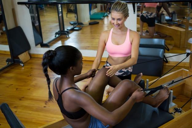 改質器のピラティスを持つ女性を支援するトレーナーの笑顔