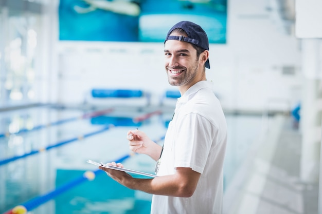 Smiling trainer holding clipboard at the pool