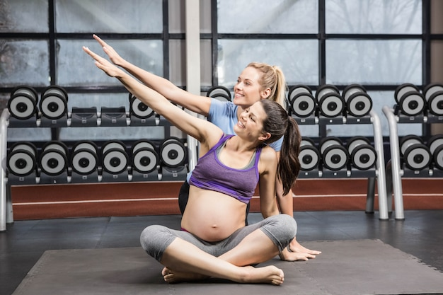 Smiling trainer and pregnant woman overstretching arm at the gym