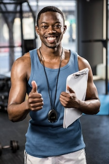 Smiling trainer showing thumbs up at the crossfit gym