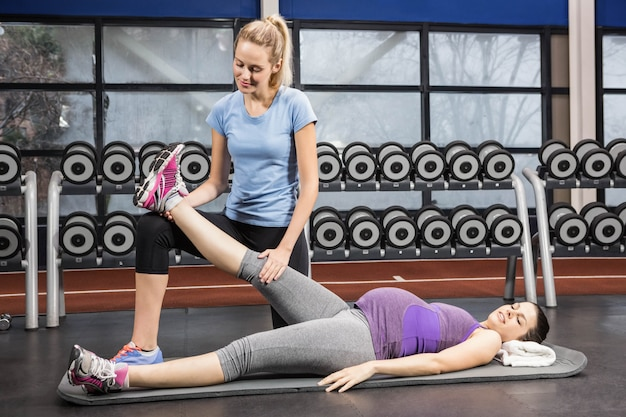 Smiling trainer stretching pregnant womans leg at the gym