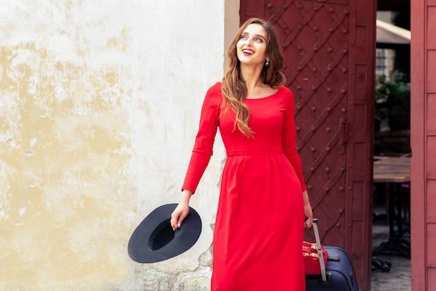 Улыбающаяся девушка путешествия идет по улице города с чемоданом и черной шляпе.