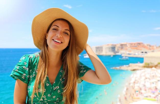 Улыбающаяся девушка путешественника в шляпе в хорватии. счастливая молодая женщина, посещающая старый город дубровник на средиземном море.