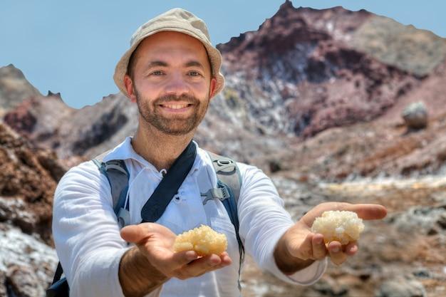 이란 호르 모즈 간 주 호르 무즈 섬에있는 암염의 큰 조각이있는 카메라 손바닥을 웃는 여행자.