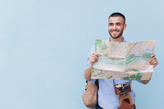 Smiling traveler photographer holding map and looking away standing against blue backdrop