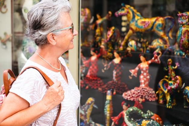 Улыбающаяся женщина старшего путешественника посещает барселону, глядя на художественные творения в витрине магазина. счастливый пенсионер, наслаждаясь отпуском