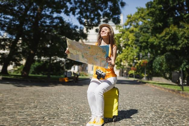캐주얼한 옷을 입은 웃고 있는 여행자 관광 여성, 도시 야외에서 도시 지도 검색 경로를 들고 여행 가방에 앉아 모자. 주말 휴가를 여행하기 위해 해외로 여행하는 소녀. 관광 여행 라이프 스타일.