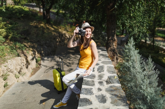 여행 가방 도시 지도가 있는 모자를 쓴 웃고 있는 여행자 관광 여성은 도시 야외에서 복고풍 빈티지 사진 카메라로 사진을 찍습니다. 주말 휴가를 여행하기 위해 해외로 여행하는 소녀. 관광 여행 라이프 스타일.