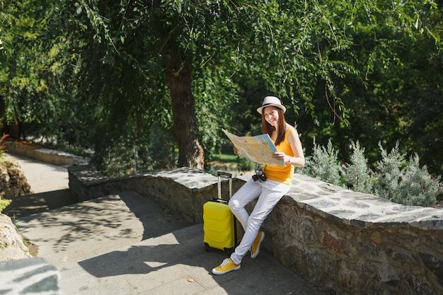 노란 옷을 입은 웃고 있는 여행자 관광 여성, 도시 야외의 돌 위에 앉아 있는 도시 지도를 들고 여행 가방을 든 모자. 주말 휴가를 여행하기 위해 해외로 여행하는 소녀. 관광 여행 라이프 스타일.
