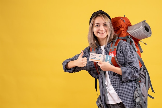 親指をあきらめてチケットを持ったバックパックを持つ笑顔の旅行者の女性