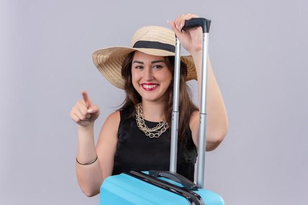 La ragazza sorridente del viaggiatore che indossa la maglietta nera nel cappello ha messo la sua mano sulla valigia e indica a lato su fondo bianco
