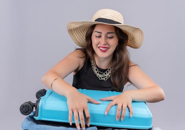 La ragazza sorridente del viaggiatore che porta la maglietta nera in cappello prova a valigia chiusa su fondo bianco
