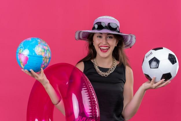 Улыбающаяся молодая девушка путешественника в черной майке в шляпе держит надувной круг и мяч с глобусом на красном фоне
