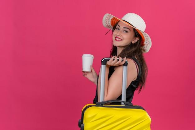 Улыбающаяся молодая девушка путешественника в черной майке в шляпе держит чемодан и чашку кофе на красном фоне
