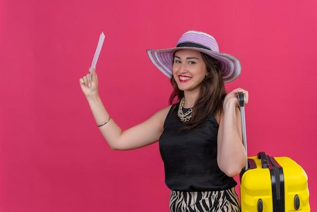 Улыбающаяся молодая девушка путешественника в черной майке в шляпе держит чемодан и билеты на красном фоне