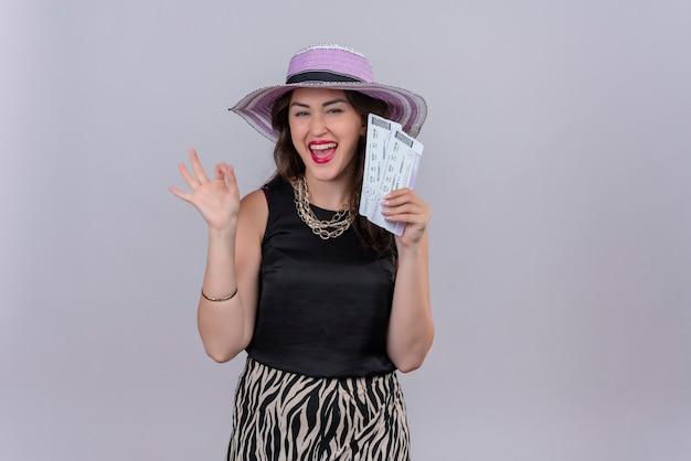 Улыбающаяся молодая девушка путешественника в черной майке в шляпе держит билеты и показывает жест на белом фоне