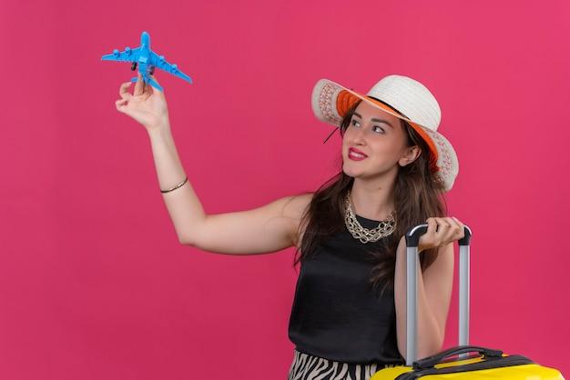 Улыбающаяся молодая девушка путешественника в черной майке в шляпе играет на игрушечном самолете на красном фоне