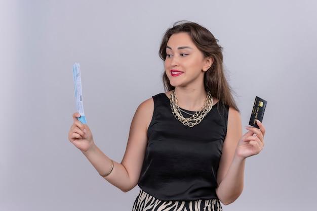 白い背景に黒のアンダーシャツの古いチケットとクレジットカードを身に着けている旅行者の少女の笑顔