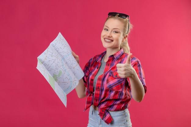 Улыбающаяся молодая девушка путешественника в красной рубашке и очках на голове держит карту большим пальцем на изолированном розовом фоне