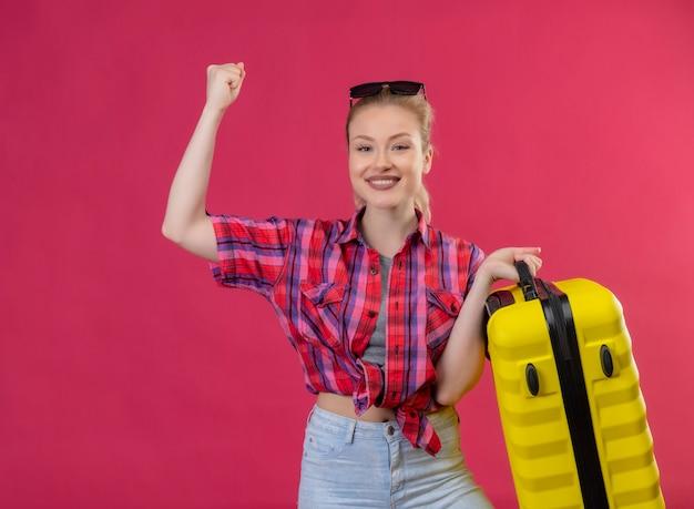 Улыбающаяся молодая девушка путешественника в красной рубашке и очках на голове держит чемодан и делает сильный жест на изолированном розовом фоне
