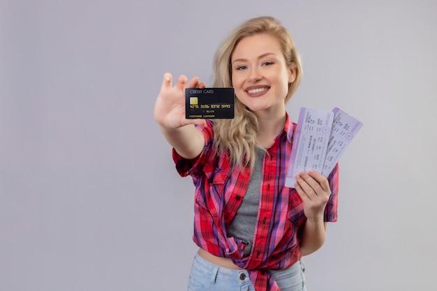 孤立した白い背景の上のクレジットカードとチケットを保持している赤いシャツを着て旅行者の少女の笑顔