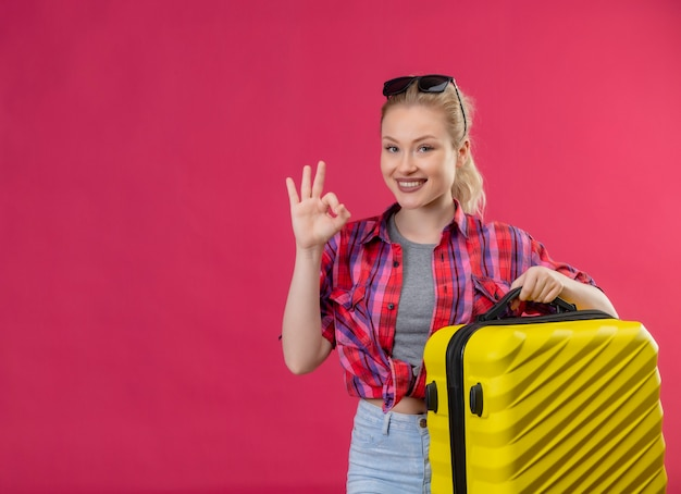 Smiling traveler young girl wearing red shirt holding suitcase shows oker gesture on isolated pink background