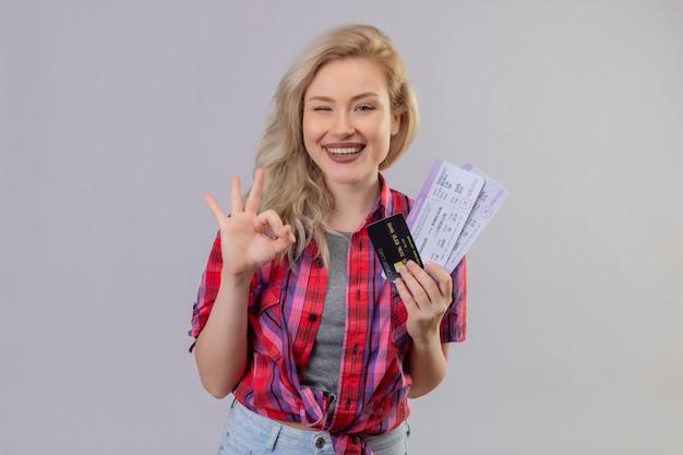 Улыбающаяся молодая девушка путешественника в красной рубашке держит билеты, показывая жест окей на изолированном белом фоне
