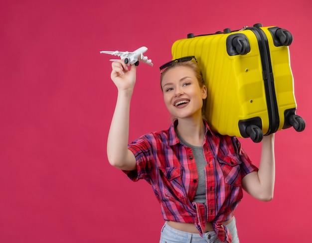 Улыбающаяся молодая девушка путешественника в красной рубашке в очках держит чемодан на плече и играет с игрушечным планом на изолированном розовом фоне