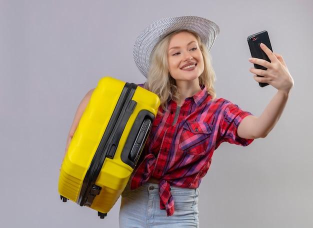 Улыбающаяся молодая девушка путешественника в красной рубашке в шляпе держит чемодан и делает селфи на изолированном белом фоне