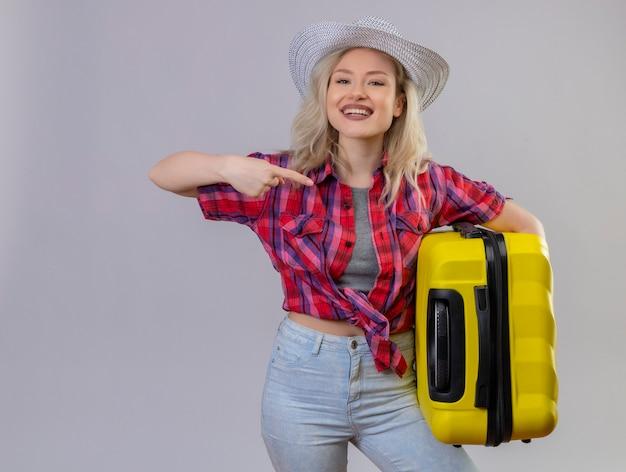 分離の白い背景の側にスーツケースポイントを保持している帽子に赤いシャツを着て旅行者の少女の笑顔