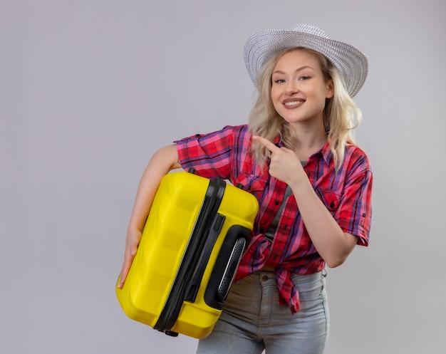 Улыбающаяся молодая девушка путешественника в красной рубашке в шляпе, держащая чемодан, указывает в сторону на изолированном белом фоне