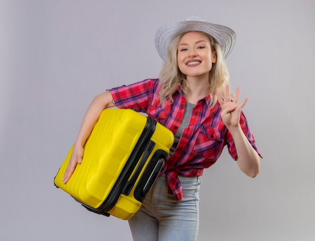 Улыбающаяся молодая девушка путешественника в красной рубашке в шляпе держит чемодан, показывая четыре на изолированном белом фоне