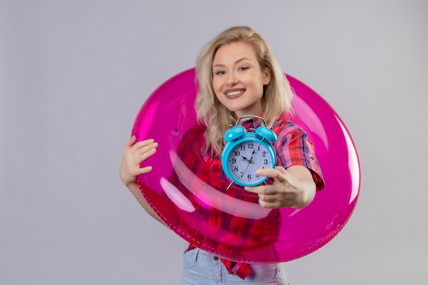 Smiling traveler young girl wearing red shirt in inflatable ring held out alarm clock to camera on isolated white background