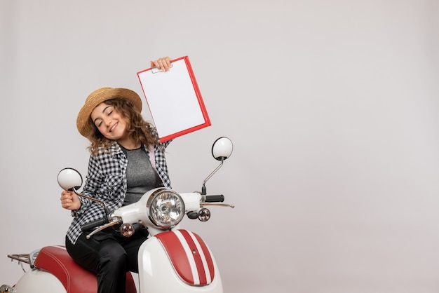 Sorridente ragazza viaggiatrice sul motorino che regge appunti rossi