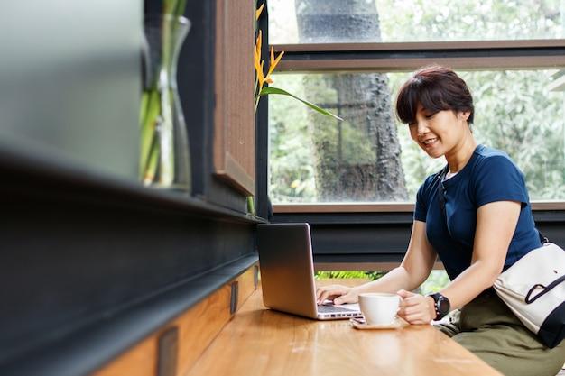 Улыбаясь женщина-путешественник, проверка бронирования план путешествия на ноутбуке, сидя в кафе
