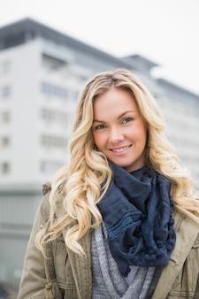 Smiling trendy blonde posing outdoors