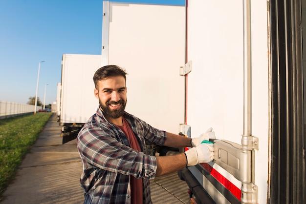 Улыбающийся водитель грузовика в рабочих перчатках открывает или закрывает задние двери прицепа грузовика, проверяя товары для транспортировки