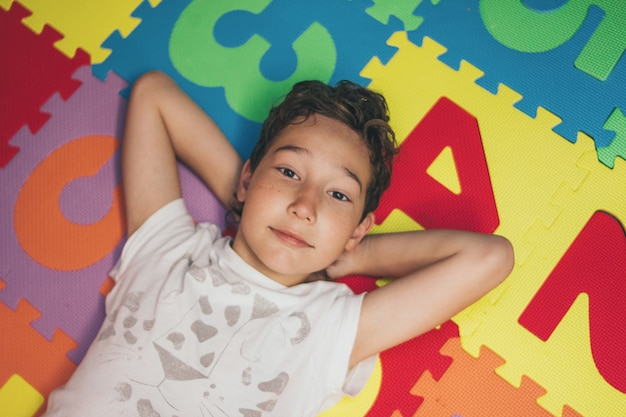 Smiling tween boy lies on colorful mat with numbers and looks at camera, view from top