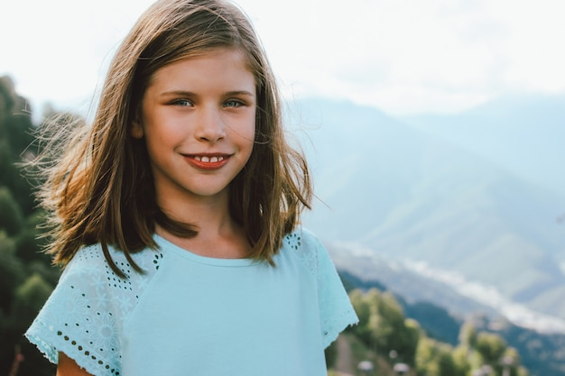 Smiling tween girl looking at camera on background of beautiful mountains