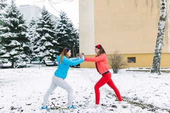 Smiling two female friends fighting at outdoors in winter