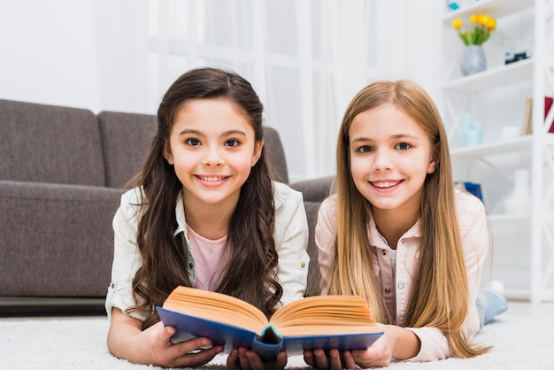 Smiling two female friends lying on carpet holding book in hand