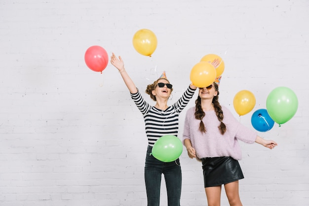 Smiling two female friends standing against white wall playing with colorful balloons