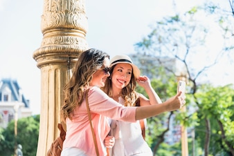Smiling two female tourist standing near the pillar talking selfie from cellphone