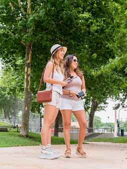 Smiling two female tourist standing in the park holding map and camera