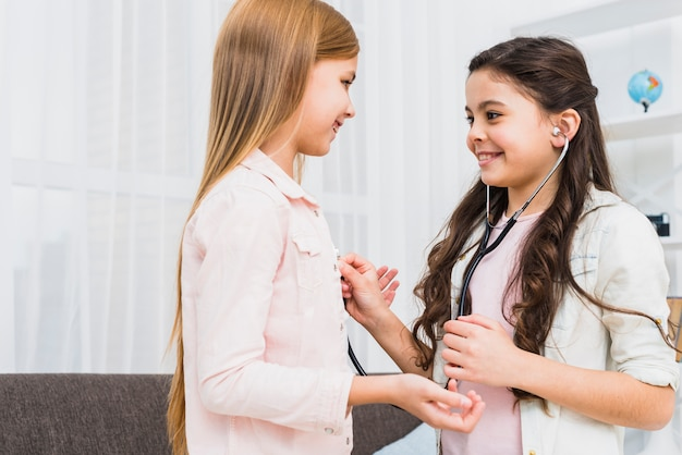 Smiling two girls enjoying playing doctor and hospital using stethoscope at home